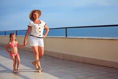 De vrouw en het meisje lopen op veranda dichtbij zeekust royalty-vrije stock afbeeldingen