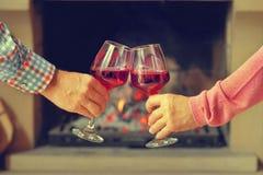 De vrouw en de man drinken wijn op de achtergrond van de open haard stock fotografie