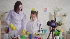 De vrouw en de tiener blogger, mengen de reagentia in een chemisch laboratorium stock video