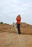 De vrouw fotografeert archeologische uitgravingen, die zich op een ladder bevinden stock fotografie