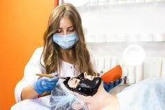 De vrouw gaat behandelingsmasker over gezichts stock afbeeldingen