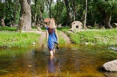 De vrouw gaat geleidelijke torrential waterstroom Royalty-vrije Stock Foto