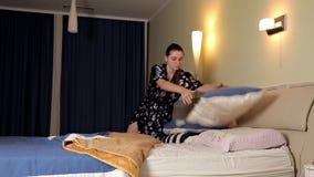 De vrouw gaat naar bed Zij ligt op het bed, in de slaapkamer en alvorens naar bed te gaan zij gebruikt de telefoon Het meisje stock video