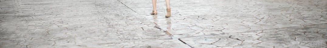 De vrouw gaat op de straat Benengewas Textuur van de oude weg met barsten Asfaltoppervlakte op de straat De banner van het Web Stock Fotografie
