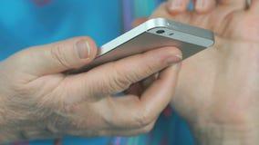 De vrouw gaat tekst binnen op zilveren cellphone in stock footage