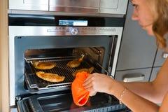 De vrouw gaat vlees van de oven weg royalty-vrije stock foto's