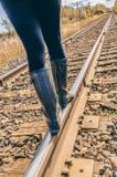 De vrouw gaat weg, in evenwicht brengend, op het spoorwegspoor, met warm v royalty-vrije stock foto