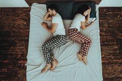 De vrouw gebruikt Cellphone en de Mens Liggend op Bed royalty-vrije stock fotografie