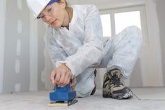 De vrouw gebruikt elektrische schuurmachine op houten vloer stock afbeelding