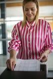 De vrouw gebruikt kopieerapparaat Onderneemster die fotokopieerapparaat in o met behulp van Royalty-vrije Stock Afbeelding