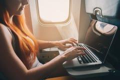 De vrouw gebruikt laptop terwijl op een vliegtuig Stock Foto