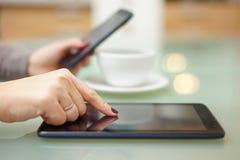 De vrouw gebruikt tabletpc en slimme telefoon in keuken bij hetzelfde stock afbeeldingen