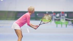 De vrouw is geconcentreerd en treft voorbereidingen om de tennisbal te raken stock footage
