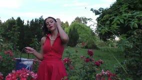 De vrouw geeft bloemen water stock video