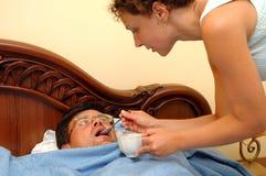 De vrouw geeft drank aan de zieke mens Royalty-vrije Stock Foto