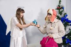 De vrouw geeft een gift aan een meisje in een engelenkostuum royalty-vrije stock fotografie