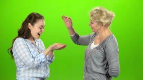 De vrouw geeft de sleutels aan haar dochter Het groene scherm Zachte nadruk stock video