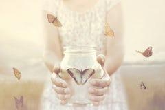 De vrouw geeft vrijheid aan sommige die vlinders in een glasvaas wordt ingesloten stock afbeelding