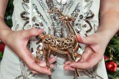 De vrouw is gekleed in een slimme kleding houdend een hert Vrouwelijke handen stock afbeeldingen