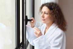 De vrouw gekleed in witte badjas houdt glas royalty-vrije stock afbeelding