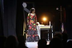 De vrouw in gekleurde kleding voert binnenshuis Flamenco Flamenqueria uit Royalty-vrije Stock Afbeelding