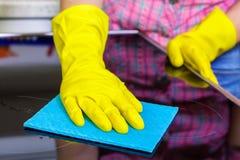 De vrouw in gele rubber beschermende handschoenen maakt elektrisch kooktoestel schoon stock foto