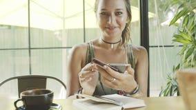 De vrouw is gelukkig voor online het kopen van kleding met smartphone in koffie stock footage