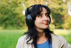 De vrouw geniet in openlucht van de muziek Stock Foto's