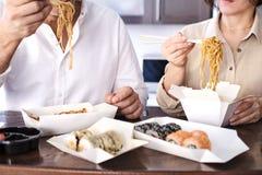 De vrouw geniet thuis van Japanse Thaise maaltijd royalty-vrije stock afbeeldingen