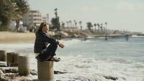 De vrouw geniet van aard werpend stenen in het overzees stock videobeelden