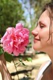 De vrouw geniet van een geur van roze toenam Royalty-vrije Stock Afbeeldingen