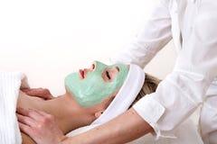 De vrouw geniet van een massage en van een gezichtsschoonheidsbehandeling. Royalty-vrije Stock Foto's