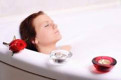 De vrouw geniet van het bad-schuim in de badkuip. Stock Foto's