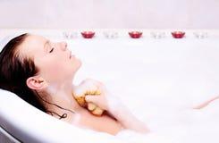 De vrouw geniet van het bad-schuim in de badkuip. Stock Fotografie