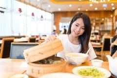De vrouw geniet van maaltijd in Chinees restaurant Royalty-vrije Stock Afbeeldingen