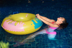 De vrouw geniet van speel haar bal in het zwembad bij nacht in het hotel stock foto
