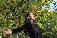 De vrouw geniet van zon in dalingstijd Stock Afbeeldingen