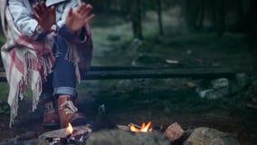 De vrouw in geruite plaid wordt verpakt die haar koude opwarmen overhandigt het kampvuur dat stock video