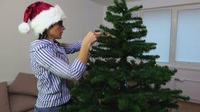 De vrouw gezette decoratie van Kerstmislichten op sparren stock videobeelden