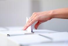 De vrouw giet haar stemming bij verkiezingen stock afbeelding