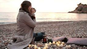 De vrouw giet hete thee in een kop en het bewonderen van de zonsondergang op het strand stock footage