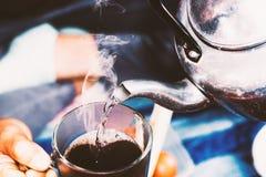 De vrouw giet kokend water in de kop van koffie Royalty-vrije Stock Fotografie
