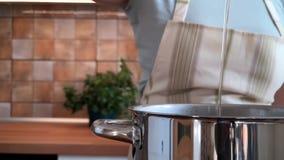 De vrouw giet olijfolie in steelpan op de keuken, langzame geanimeerde video stock videobeelden