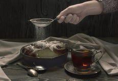 De vrouw giet suikerpoeder op pastei Stock Foto