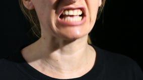 De vrouw gilt in de camera op een zwarte achtergrond Mond en grijnsclose-up stock videobeelden