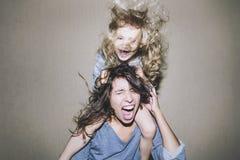 De vrouw gilt en debatteert met een kind op zijn schouders cli royalty-vrije stock fotografie