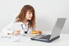 De vrouw ging achter lijst op kantoor eten stock afbeelding