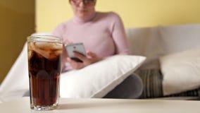 De vrouw in glazen brengt tijd door thuis, gebruikt de telefoon en drinkt whisky met Coca-cola stock video