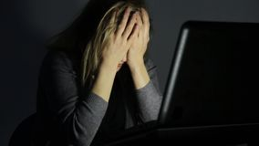 De vrouw in glazen die computer in een donkere ruimte met behulp van, bekijkt de monitor en begint gefrustreerd te worden