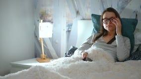De vrouw in glazen ligt in een bed en gebruikt een smartphone vóór bedtijd stock videobeelden
